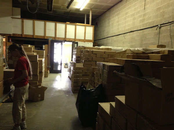 Keliana Tayler, with stacks of boxes full of thousands of books